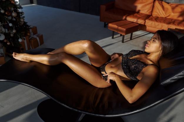 Femme sexy en lingerie noire posant dans un lit de bronzage en cuir