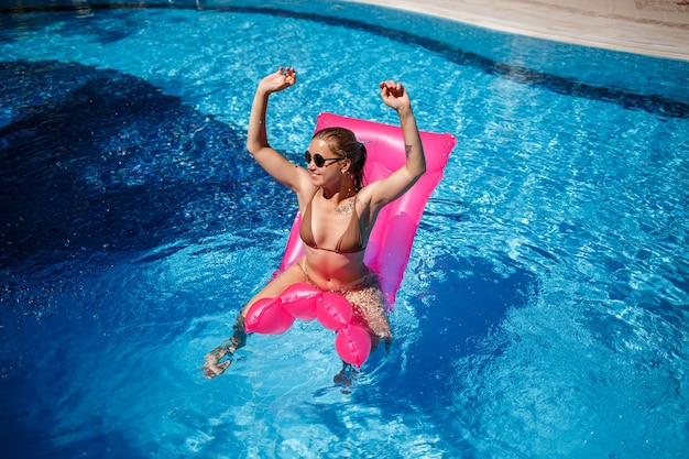 Femme sexy à lunettes de soleil se reposant et se faisant bronzer sur un matelas rose dans la piscine. jeune femme en maillot de bain bikini beige flottant sur matelas rose gonflable