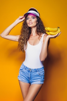 Femme sexy en maillot de bain blanc et short en jean bleu, visière à la mode tenant des bananes et posant isolé sur jaune