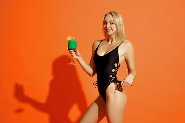 Femme sexy en maillot de bain pose avec cocktail sur orange