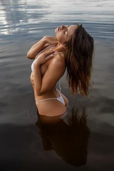 Femme sexy en maillot de bain sur la rive du fleuve
