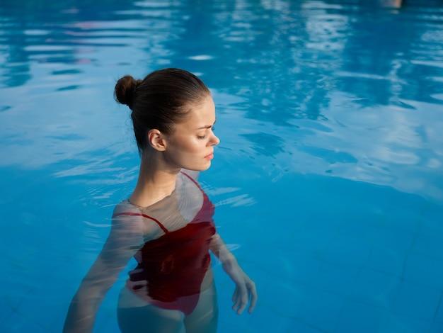 Femme sexy en maillot de bain se tient aux épaules dans un modèle de vue recadrée en eau transparente
