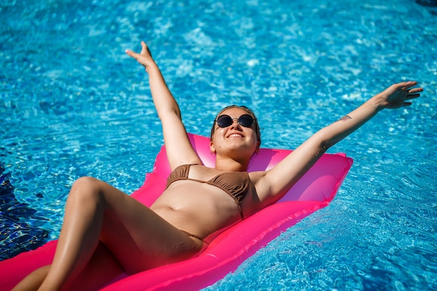 Une femme sexy en maillot de bain se trouve sur un matelas gonflable rose dans la piscine. détendez-vous au bord de la piscine par une chaude journée ensoleillée d'été. concept de vacances