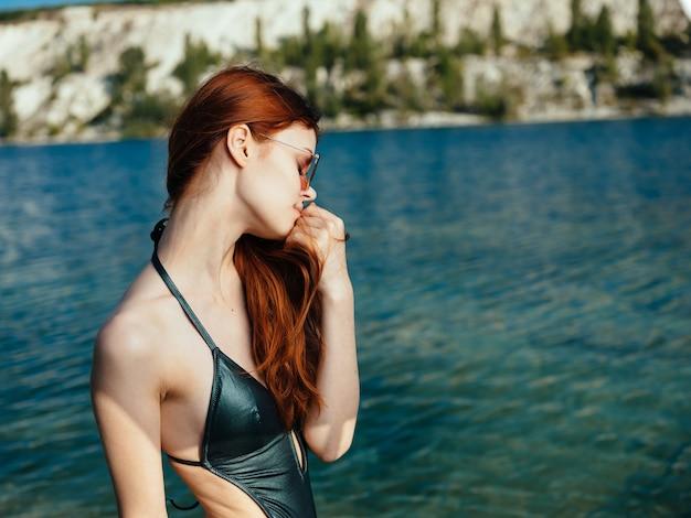 Femme sexy en maillot de bain vert et lunettes près d'une rivière transparente dans la nature.
