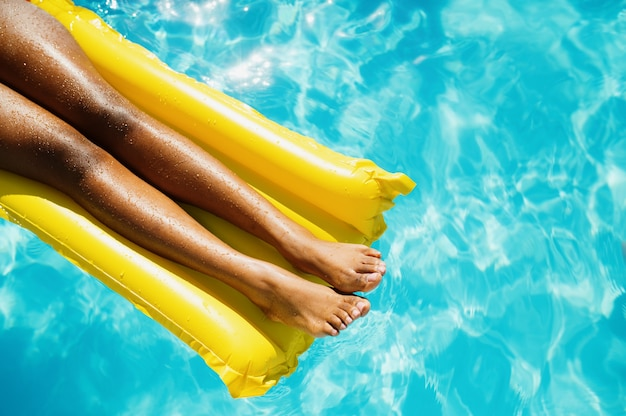 Une femme sexy nage sur un matelas dans la piscine, vue de dessus
