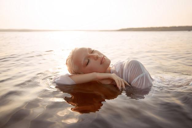Femme sexy nue nue dans l'eau au coucher du soleil. belle femme blonde aux cheveux mouillés courts et gros seins, portrait d'art en mer
