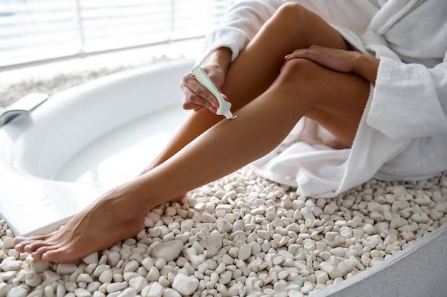 Femme sexy en peignoir assis sur le bord de la baignoire. personne de sexe féminin dans la baignoire, soins de beauté et de santé au spa, traitement de bien-être dans la salle de bain, cailloux et bougies sur fond