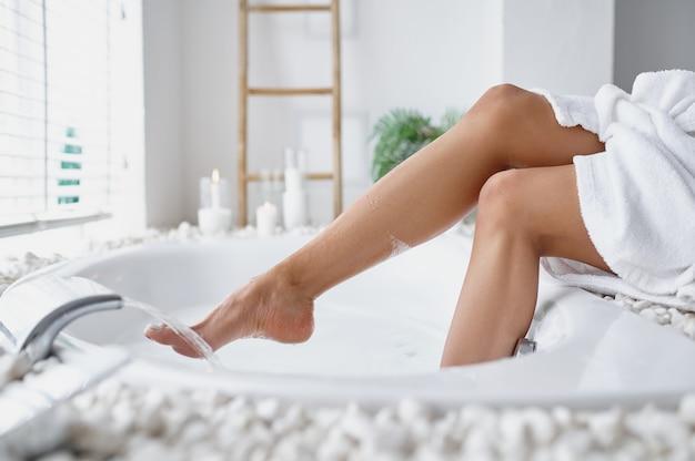 Femme sexy en peignoir mouille ses pieds dans le bain. personne de sexe féminin dans la baignoire, soins de beauté et de santé au spa, traitement de bien-être dans la salle de bain, cailloux et bougies sur fond