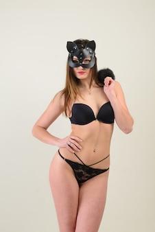 Femme sexy portant un déguisement de catwoman, masque, sous-vêtements séduisants, studio