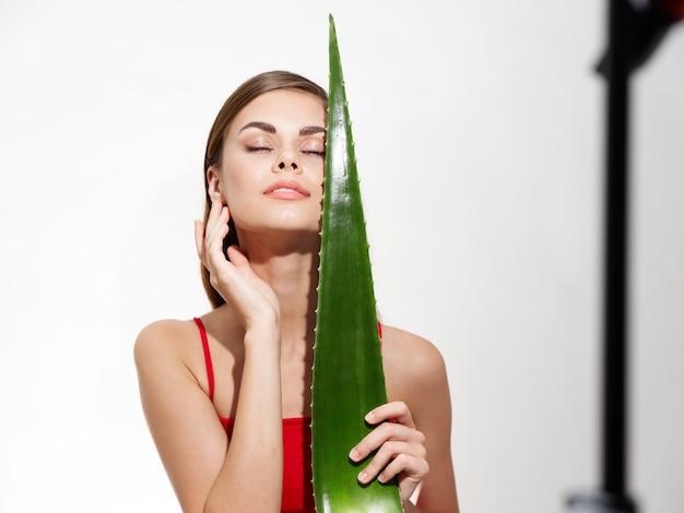 Femme sexy avec le portrait de modèle de cosmétologie de peau propre de feuille d'aloès vert