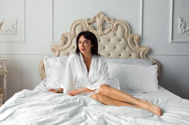 Femme sexy posant dans la chambre vêtue d'une robe de soie blanche