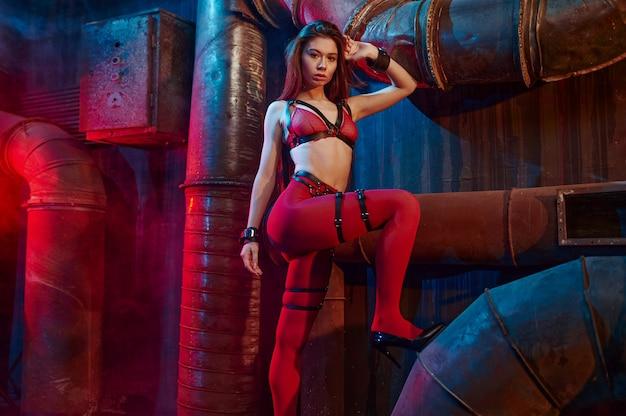 Femme sexy pose en bas bdsm rouges, intérieur d'usine abandonnée. jeune fille en sous-vêtements érotiques, fétichisme sexuel, fantaisie sexuelle