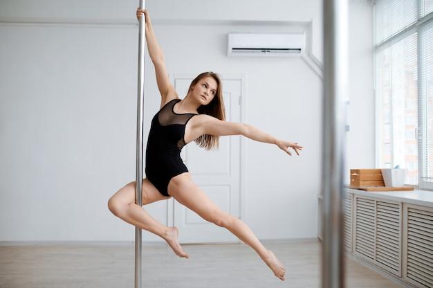 Femme sexy pratique la pole dance, entraînement en classe. danseuses professionnelles exerçant dans une salle de sport, pole-dance
