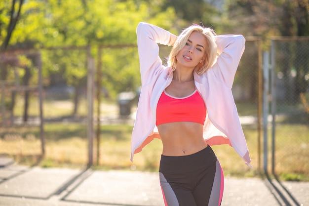 La femme sexy de remise en forme mince porte un vêtement de sport posant en journée ensoleillée. espace libre