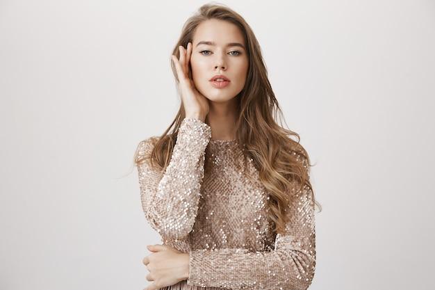 Femme sexy en robe de soirée semble sensuelle