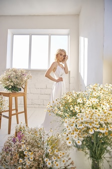 Femme sexy romantique dans une longue robe de mariée blanche se tient près de la fenêtre en fleurs de camomille. fille blonde avec une silhouette parfaite