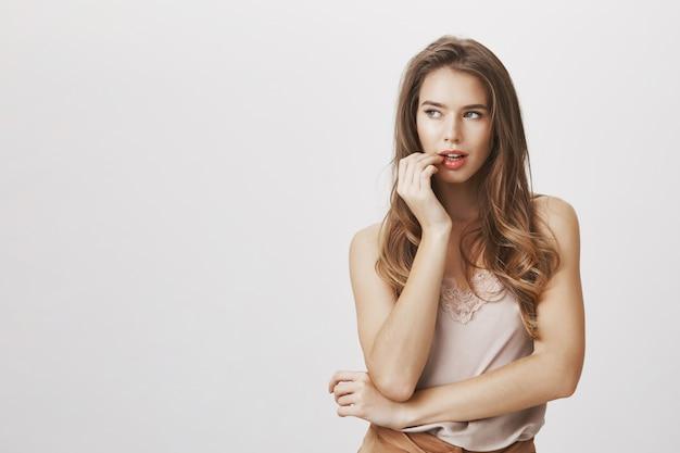 Femme sexy se mordant le doigt et regarde à gauche avec désir