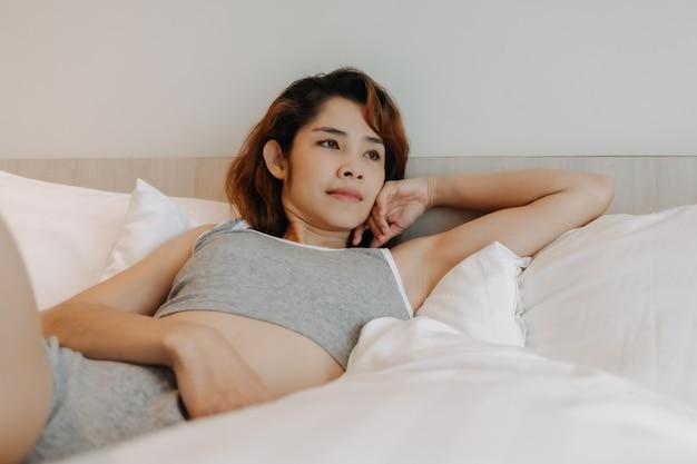 Une femme sexy se sent se détendre sur le lit seule dans la chambre