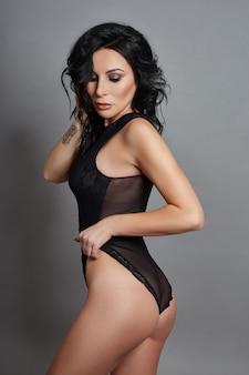 Femme sexy avec une silhouette parfaite et de gros seins posant sur un fond gris