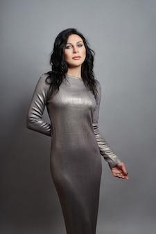 Femme sexy avec une silhouette parfaite et de gros seins posant sur un mur gris.