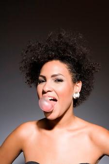 Femme sexy soufflant bulle bulle de gomme, portrait en studio