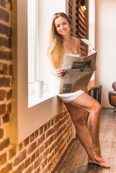 Femme sexy souriante se penchant près de fenêtre tenant le journal
