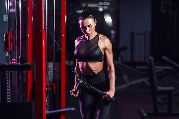 Femme sexy sportive, faire de l'exercice en utilisant la machine dans la salle de gym - vue latérale