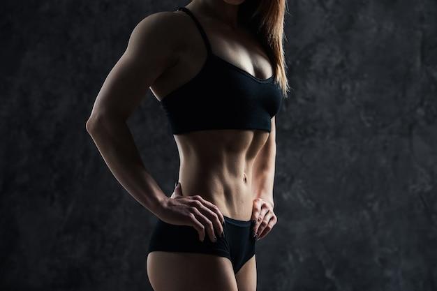 Femme sexy sportive avec gros ventre musculaire dans un vêtement de sport noir