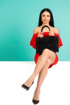 Femme sexy en talons hauts avec sac à main noir sur fond bleu