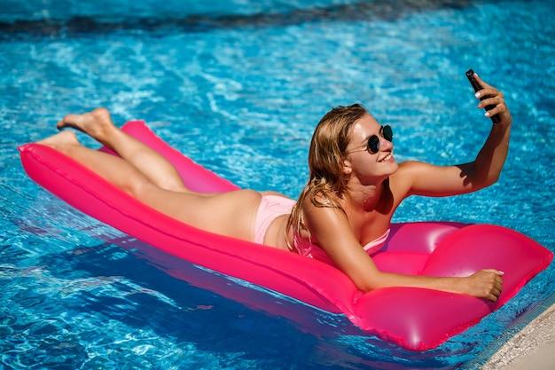 Une femme sexy avec un téléphone en maillot de bain se trouve sur un matelas gonflable rose dans la piscine. détendez-vous au bord de la piscine par une chaude journée ensoleillée d'été. concept de vacances