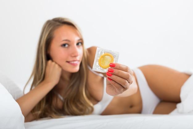 Femme sexy tenant le préservatif au lit