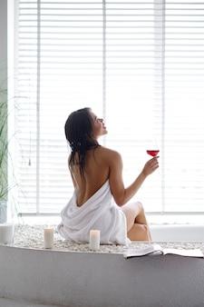 Femme sexy avec verre assis sur le bord de la baignoire, vue arrière. personne de sexe féminin dans la baignoire, soins de beauté et de santé au spa, traitement de bien-être dans la salle de bain, cailloux et bougies sur fond