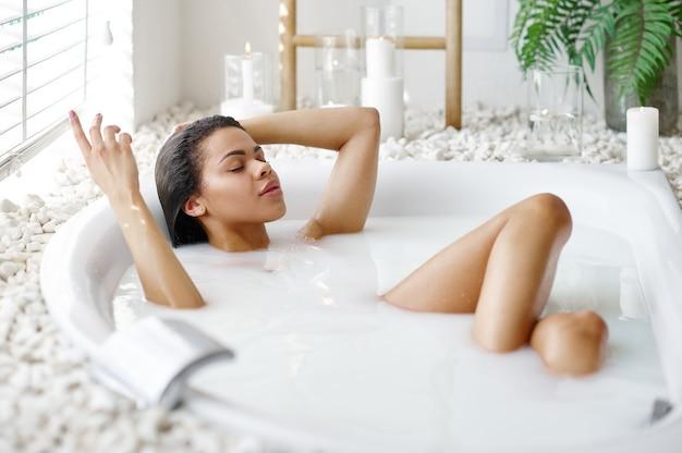 Femme sexy avec un verre de boisson dans le bain avec du lait. personne de sexe féminin dans la baignoire, soins de beauté et de santé au spa, traitement de bien-être dans la salle de bain, cailloux et bougies sur fond