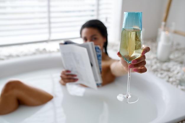 Une femme sexy avec un verre lit un magazine dans un bain avec du lait. personne de sexe féminin dans la baignoire, soins de beauté et de santé au spa, traitement de bien-être dans la salle de bain, cailloux et bougies sur fond