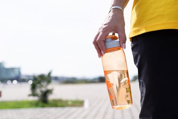 Femme avec le shaker dans sa main à l'extérieur dans le parc