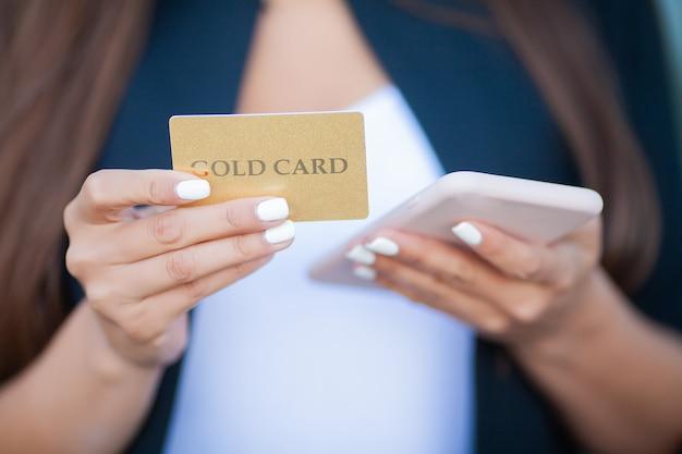 Femme shopping avec carte de crédit. belle jeune femme avec une carte en or à l'aide de téléphone