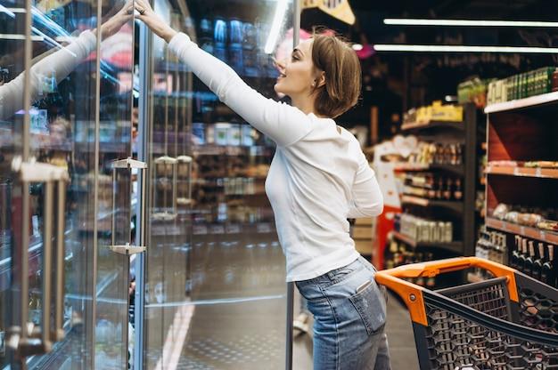 Femme shopping à l'épicerie, près du réfrigérateur