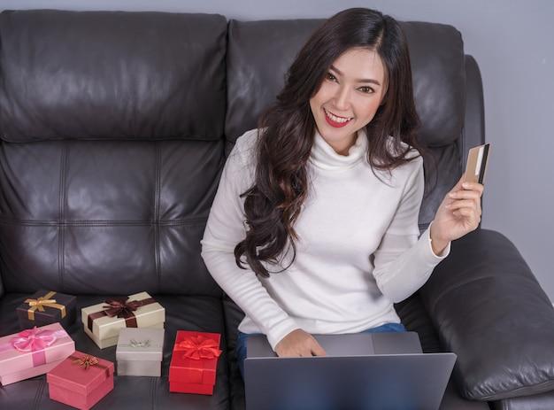 Femme shopping en ligne pour cadeau avec ordinateur portable dans le salon