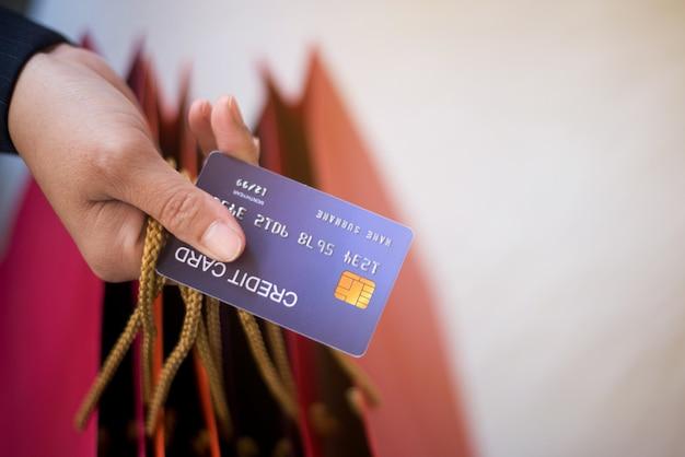 Femme shopping de nombreux produits lors de la vente. payer pour les produits de carte de crédit pendant la saison des fêtes.