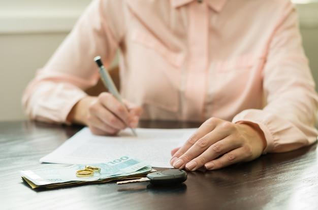 Femme signant un accord de divorce avec de l'argent, clé de voiture sur la table