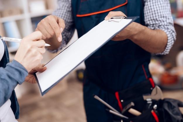 Une femme signe un acte de travail effectué par un réparateur.