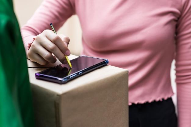 Femme signe signature sur smartphone au-dessus de la boîte en carton transporter par livreur