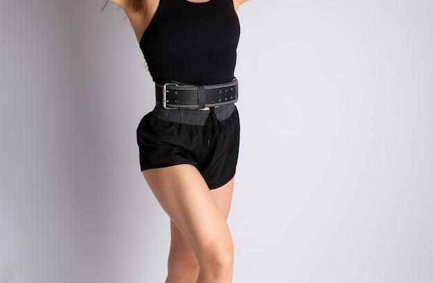 Femme avec une silhouette athlétique vêtue d'un short noir et d'une ceinture de sport en cuir