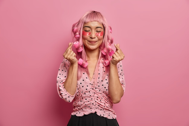 Femme sincère et positive avec de longs cheveux roses, applique des rouleaux, fait une coiffure frisée, montre un signe de cœur coréen, porte des patchs de collagène rose pour réduire les poches