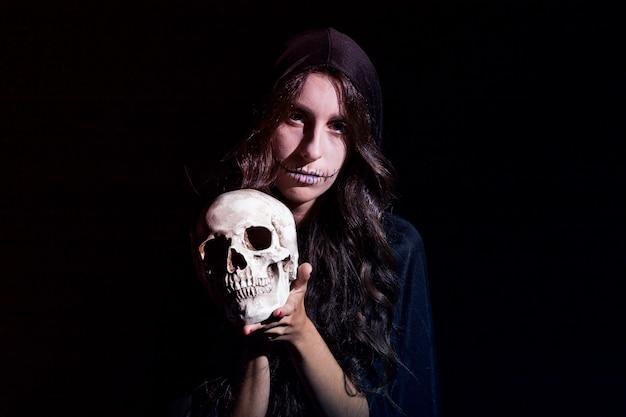 Femme sinistre avec un crâne humain