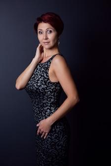 Une femme sinueuse dans une robe noire pose sur un fond sombre