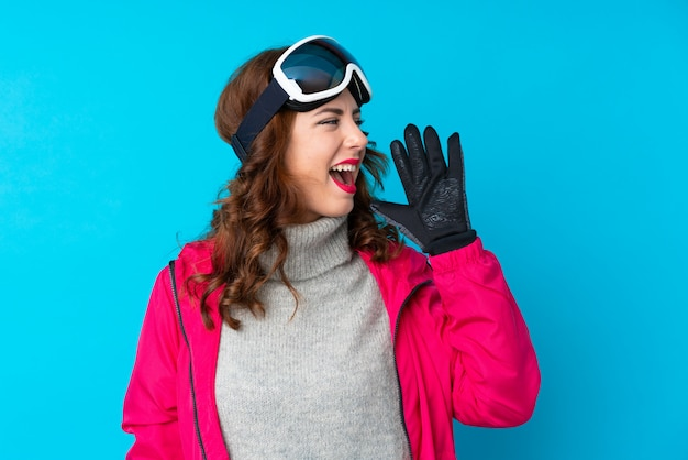 Femme de skieur avec des lunettes de snowboard sur mur bleu isolé criant avec la bouche grande ouverte