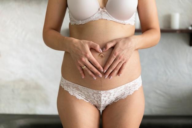 Femme en slip faisant un coeur sur son ventre