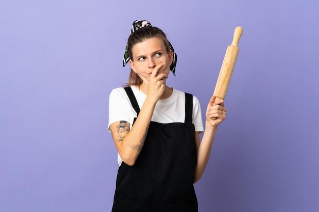 Femme slovaque cuisinière isolée sur mur violet ayant des doutes et avec l'expression du visage confus