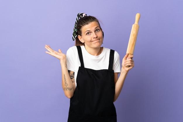 Femme slovaque cuisinière isolée sur mur violet faisant le geste de doutes